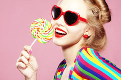 Lollipop. Glamourous girl wearing heart shaped sunglasses holding lollipop stock images