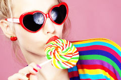 Lollipop. Glamourous girl wearing heart shaped sunglasses holding lollipop royalty free stock images