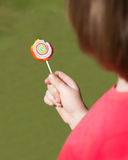 Lollipop. Young girl eating a spiral lollipop stock images
