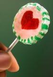 Lollipop. In fingers on green background stock photo
