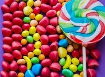 Ζωηρόχρωμο lollipop στις διεσπαρμένες καραμέλες Στοκ φωτογραφία με δικαίωμα ελεύθερης χρήσης