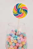 Lollipop. Colorful beads on a glass of wine . In light sweet warm tone Royalty Free Stock Image