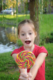 Lollipop. Cute girl eating a colorful big lollipop stock photos