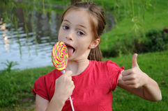 Lollipop. Cute girl eating a colorful big lollipop stock photo