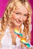 Lollipop de sorriso curly louro da terra arrendada da menina Fotografia de Stock Royalty Free