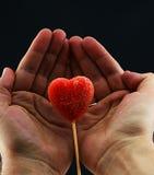 Lollipop del corazón sostenido en manos Imágenes de archivo libres de regalías
