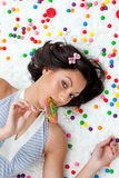 Lollipop girl. Young Latina woman laying on ruffled cloud like floor between colorful bubblegum balls eating a lollipop royalty free stock image