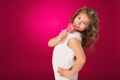 Lollipop. The girl with a sweet heart-shaped candy Stock Photos