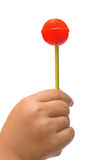 Lollipop in the hand of a child Stock Photos
