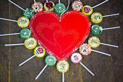 Lollipop heart-shaped, wooden background, with inside a heart Royalty Free Stock Photos
