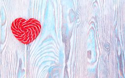 Lollipop heart on vintage blue wooden background. Empty space for your text. Valentine day postcard. Royalty Free Stock Image