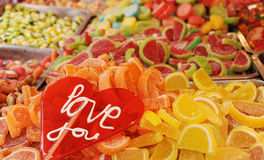 Lollipop with love you words and piles of colored candies as a background Royalty Free Stock Photo