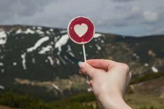 Lollipop patterned heart in hand woman against  of the mountains.  Stock Photo
