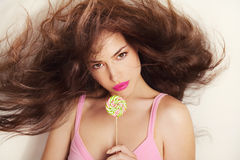 Lollipop. Pretty girl with big flying hair holding lollipop, studio white stock photography