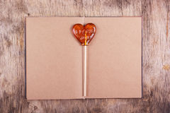 Lollipop in the shape of a heart and an old diary with blank pages. Stock Photography