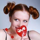 lollipop sonriente del corazón de la explotación agrícola de la muchacha Foto de archivo libre de regalías