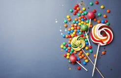 Lollipops και ζωηρόχρωμες καραμέλες στο γκρίζο υπόβαθρο, τοπ άποψη στοκ εικόνες