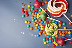 Lollipops και ζωηρόχρωμες καραμέλες στο γκρίζο υπόβαθρο, τοπ άποψη στοκ εικόνες με δικαίωμα ελεύθερης χρήσης