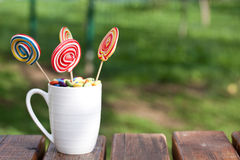 Lollipops. With dragees in the mug Royalty Free Stock Image