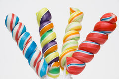 Lollipops. Twisted brightly colored candies on stick against a white background royalty free stock photos