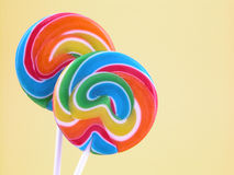 Lollipops. Two colorful lollipops on yellow background Royalty Free Stock Images