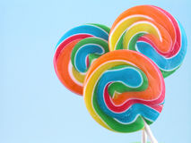 Lollipops. Three colorful lollipops on blue background Royalty Free Stock Images