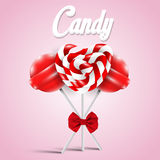 Lollipops with a bow on pink background Stock Photos