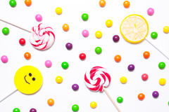 Lollipops, candy smile on, are scattered around the colorful jel. Ly beans on a white background. flat Stock Image