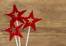 Lollipops in star shape on wooden background Stock Photos