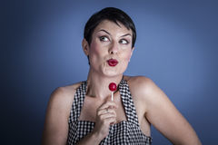 Lolly, happy young woman with lollypop  in her mouth on blue bac Royalty Free Stock Photography