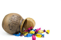 Ceramic candy jar. Tipped over ceramic lolly jar with colorful wrapped lollies Royalty Free Stock Photo