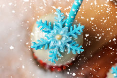 Lollypop closeup on the snow, surrounded by falling snowflakes. Stock Photo