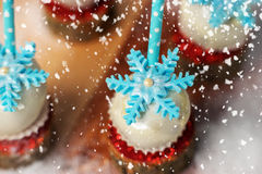 Lollypop closeup on the snow, surrounded by falling snowflakes. Studio light. Stock Photography