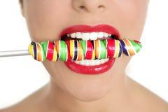 Lollypop colorido nos dentes perfeitos da mulher Fotografia de Stock