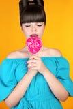 Lollypop godis Härlig tonårig flicka som äter färgglad hjärtalolli Royaltyfri Bild