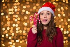 滑稽的逗人喜爱的女孩在有圣诞节lollypops的圣诞老人帽子 免版税库存图片