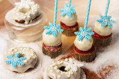 Lollypops zijaanzicht over de sneeuw en een paar donuts Close-up stock fotografie