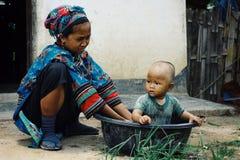 lolo stammenvrouw die een bad geven aan haar jong geitje in een emmer royalty-vrije stock foto