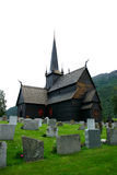 Lom Stave Church and cemetery - vertical. The Lom Stave Church is a triple nave stave church and amongst the oldest of Norway Stock Photography