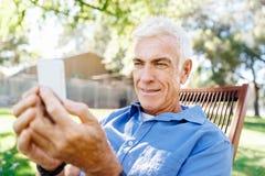 LoMature man som använder utomhus mobiltelefonen Arkivbild