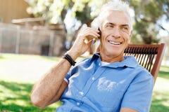 LoMature man som använder utomhus mobiltelefonen Royaltyfri Bild
