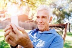 LoMature man som använder utomhus mobiltelefonen Royaltyfria Foton