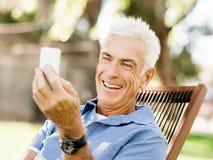 LoMature man som använder utomhus mobiltelefonen Fotografering för Bildbyråer