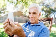 LoMature man som använder utomhus mobiltelefonen Royaltyfri Foto
