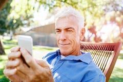 LoMature man som använder utomhus mobiltelefonen Arkivbilder