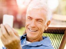 LoMature man som använder utomhus mobiltelefonen Royaltyfri Fotografi