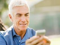 LoMature man som använder utomhus mobiltelefonen Royaltyfria Bilder