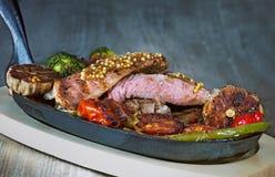 Lombinho de carne com sangue na grade com vegetais fotografia de stock