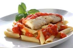 Lombo cucinato del merluzzo con la salsa di pomodori Fotografie Stock Libere da Diritti
