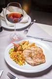 Lombo de carne de porco, prato lateral e vinho grelhados Fotos de Stock Royalty Free